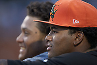 Garvis Lara (foreground) and Ricardo Cespedes of the Greensboro Grasshoppers watch the action from the dugout during the game against the West Virginia Power at First National Bank Field on August 9, 2018 in Greensboro, North Carolina. The Power defeated the Grasshoppers 9-7 in game two of a double-header. (Brian Westerholt/Four Seam Images)