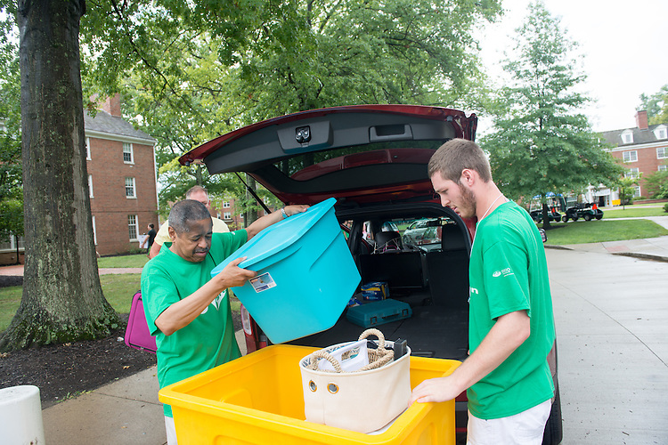 President Roderick McDavis and Go Green volunteer Michael Lively,  help first year students move into the residence halls on East Green. Photo by Ben Siegel