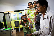 A young girl tries to distract her father's attention while he checks to confirm all data on the computer during national identity enrollment in Mysore city in Karnataka, India. Photograph: Sanjit Das/Panos