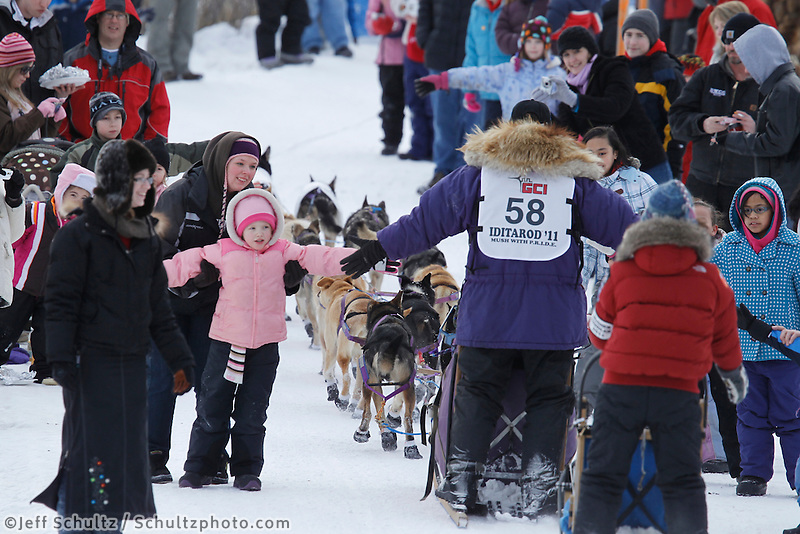 Spectators crowd the trail to get high-fives from Jessie Royer on the bike trail near the Native Hospital in mid-town Anchorage during the ceremonial start of the 2011 Iditarod
