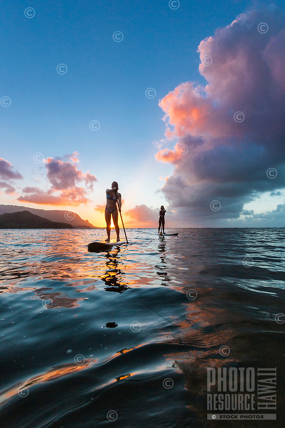 At sunset, two women stand up paddle in Hanalei Bay, Kaua'i.