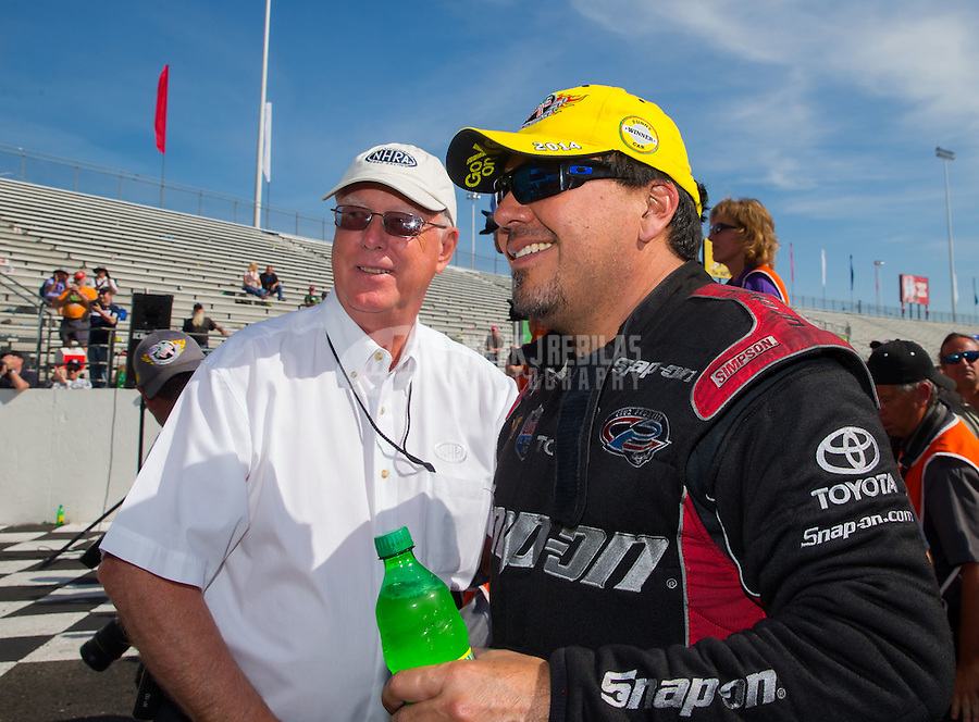 Jun. 1, 2014; Englishtown, NJ, USA; NHRA funny car driver Cruz Pedregon (right) is congratulated by NHRA official Graham Light as he celebrates after winning the Summernationals at Raceway Park. Mandatory Credit: Mark J. Rebilas-