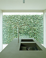 A wall of ivy provides a backdrop beyond the window of this minimal kitchen which features a stone-topped island containing two large rectangular sinks