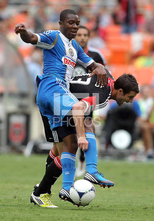 WASHINGTON, D.C. - AUGUST 19, 2012:  Chris Pontius (13) of DC United is tackled by Michael Lahoud (13) of the Philadelphia Union during an MLS match at RFK Stadium, in Washington DC, on August 19. The game ended in a 1-1 tie.
