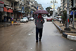 Palestinians walk in a street during a rainy day in Gaza city on January 20, 2020. Photo by Mahmoud Ajjour