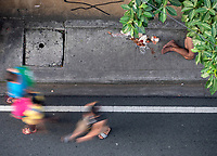 Homeless man lying on the footpath while life goes on and people passing by, Manila, Philippines