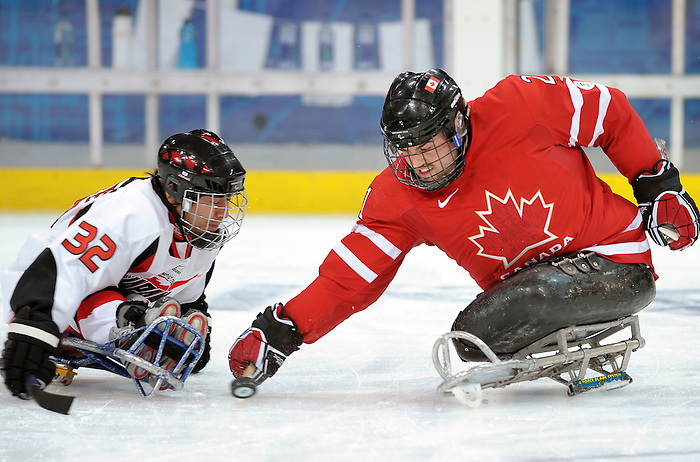 Raymond Grassi (21) reaches for the puck during 2010 Paralympic Games sledge hockey action at UBC Thunderbird Arena in Vancouver. Credit: CPC/HC/Matthew Manor.