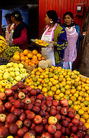 Indian women selling fruits at the market in Mexico. Oranges and apples
