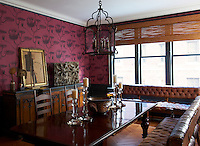 The dining room walls are covered with a dusky pink wallpaper with a botanical pattern set off against dark grey panelling and window frames
