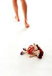 Bare legs walking away from Raggedy Ann doll