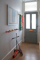 The entrance hallway has a part-glazed front door and is furnished with a row of amusing coloured pegs for clothes storage