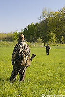 Hunter in camouflage signalling to partner in a field