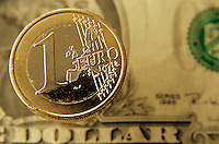 One euro coin against a us one dollar banknote
