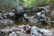 An old dam on Gibbs Brook in the New Hampshire White Mountains during the spring months. This dam, rebuilt in the 1960s, and piping system (out of sight) supplied water to the old Crawford House. The Crawford House was located where the AMC Highland Center is today. Crawford Path, the oldest continuously used mountain trail in America, passes by this dam.