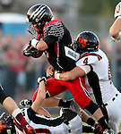 BRANDON, SD - SEPTEMBER 26: Riley Frantzen #11 from Brandon Valley bulls his way over Cole Uithoven #20 while Reagan Stenzel #4 from Washington holds on in the first quarter of their game Friday night in Brandon.  (Photo by Dave Eggen/Inertia)