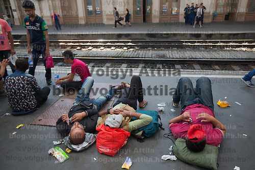 Illegal migrants sleep on the platform as they wait to board a train in hopes to leave for Germany at the main railway station Keleti in Budapest, Hungary on September 03, 2015. ATTILA VOLGYI