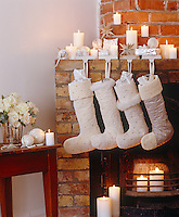A row of hand-made Christmas stockings hangs from the mantelpiece in this living room