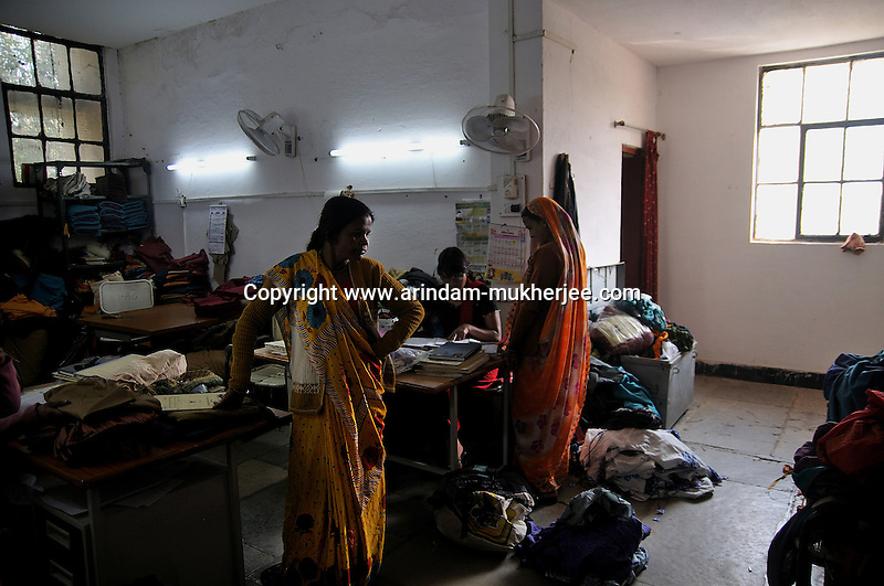 Workers submitting their weekly work to one of the employee of 'Sadhna' on the basis of which they will get their payment. Udaipur, Rajasthan, India. 24.1.2011. Arindam Mukherjee