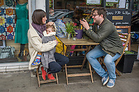 A mother breastfeeds her 15 month old boy from a sling while sitting outside a cafe.  Her partner is looking at a  photograph on the back of his camera that he has just taken of them.<br /> <br /> London, England, UK<br /> 22-03-2015<br /> <br /> &copy; Paul Carter / wdiip.co.uk