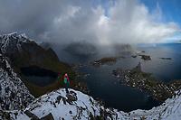 Female hiker enjoys view over Reine from summit of Reinebringen mountain peak with autumn snow, Moskenesøy, Lofoten Islands, Norway