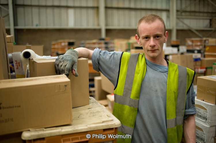 A Job Seekers Allowance claimant on a compulsory four week unpaid work placement in a warehouse on Stakehill Industrial Estate, Oldham, part of a Mandatory Work Related Activity welfare-to-work programme.