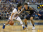 Nevada guard Jazz Johnson (22) drives past Akron's Channel Banks (11) in the first half of an NCAA college basketball game in Reno, Nev., Saturday, Dec. 22, 2018. (AP Photo/Tom R. Smedes)