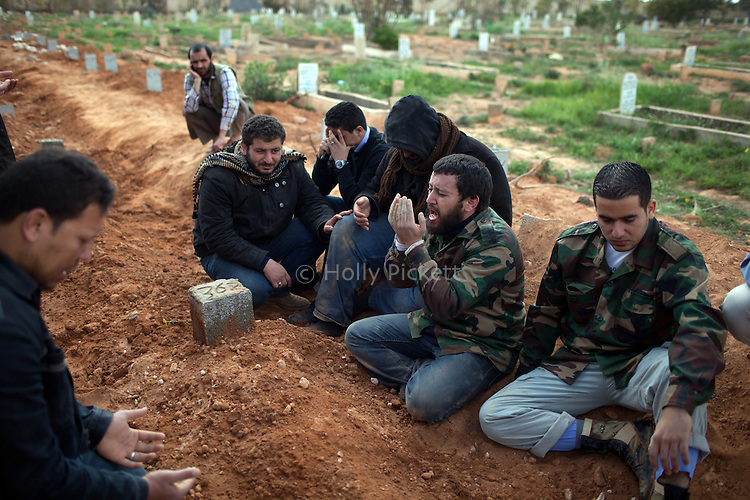 Family and friends of Mehdi Osman, 23, weep at his grave during a mass funeral for 20 people, killed during fighting between opposition rebels and loyalist forces of Col. Muammar Qaddafi, in Benghazi, Libya, March 20, 2011. Osman was a university student in business who joined the opposition rebels and was killed in fighting in Gemeis at the edge of Benghazi. The main hospital in Benghazi reported around 50 dead fighters and civilians the previous day and at least 35 on Sunday.