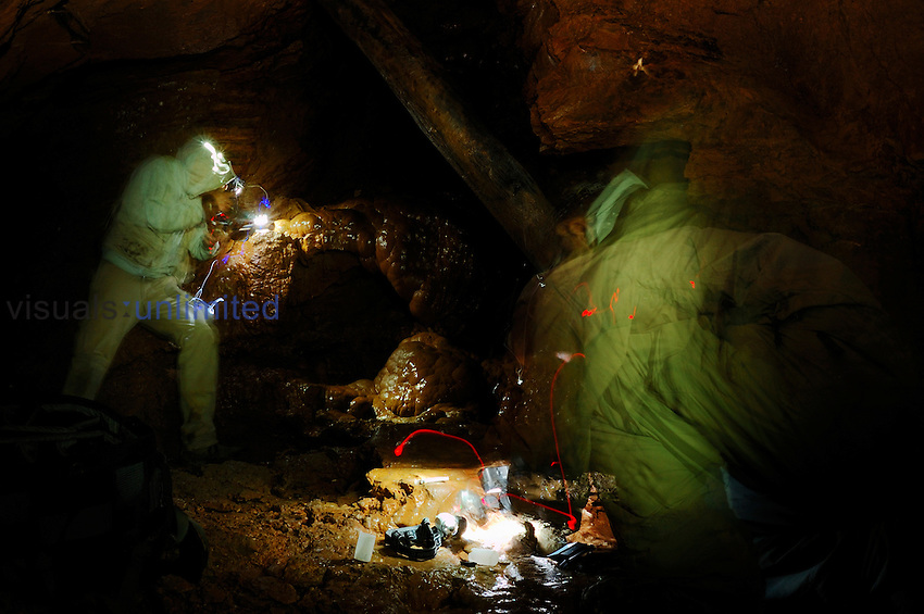 Two speleologist photographing in the deep darkness of a cave, Italy.