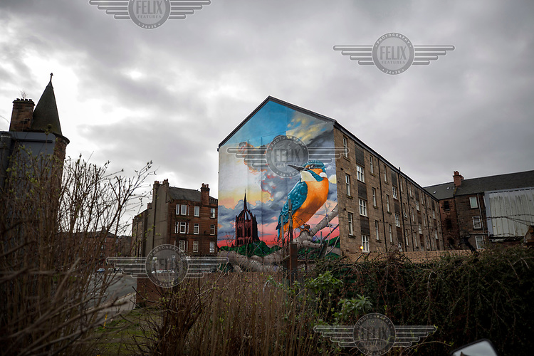 A mural depicting the Coats memorial church and a kingfisher brightens the end of a row of tenement flats, a common building style in Scotland.