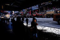 A woman walks near snow in Times Square after the pass of the winter storm JONAS, in New York, 01/24/2016. Photo by VIEWpress