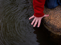 Young boy in red shirt touches water with his fingertips