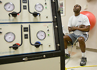 mayoheart 158497-- Charles Okeke works out at the Mayo Clinic Hospital. Once critically ill, he is now healthier due to the Total Artificial Heart, left. The Total Artificial Heart weighs 400 pounds keeping him stuck in the hospital until he can get a heart transplant or until he can be hooked up to a more portable version. (Pat Shannahan/ The Arizona Republic)