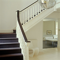 The elegant and traditional staircase ascends from a modern entrance hall with a glimpse into the contemporary living room