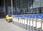 Man driving vehicle collecting trolleys at Malaga airport, Spain
