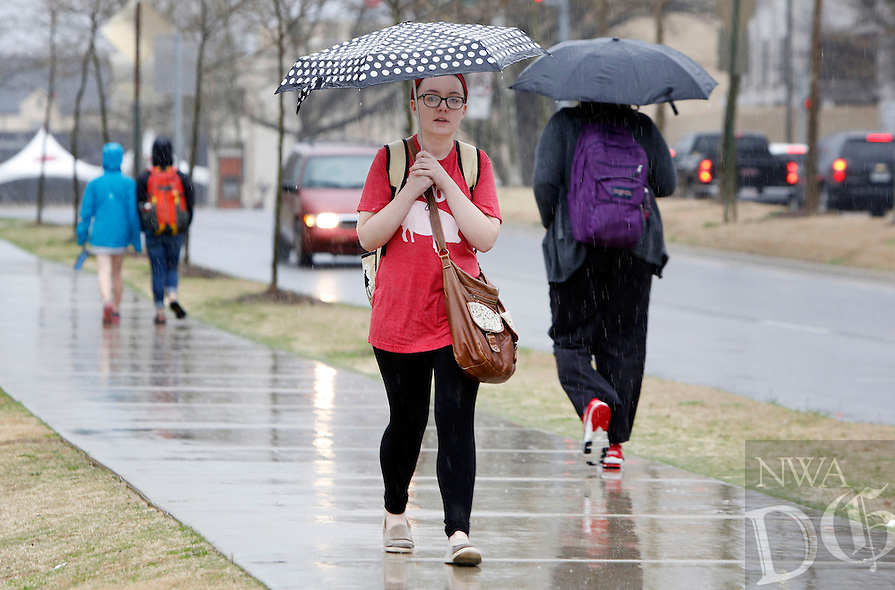 NWA Democrat-Gazette/DAVID GOTTSCHALK  Katie Pearson, a freshman at the University of Arkansas, walks in the rain Friday, March 18, 2016, on the campus in Fayetteville. Rain returned to the area Friday with low temperatures predicted to drop below freezing over night through the end of the weekend.