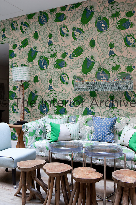 Sofa upholstered in green floral pattern fabric and beechwood stools from Sempre are placed against a backdrop of similarly patterned de Gournay wallpaper.