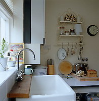 An enamel sink with a simple shelf made of rough-hewn planking in a corner of this country kitchen