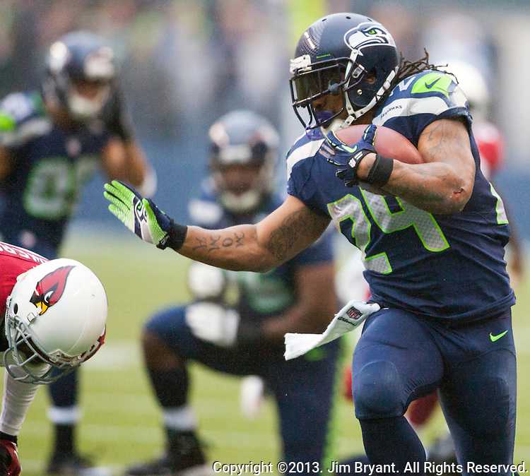 Seattle Seahawks running back Marshawn Lynch (25) stiff arms  Arizona Cardinals cornerback Jerraud Powers (25)  while running for  a first down during the 2nd quarter at CenturyLink Field in Seattle, Washington on December 22, 2013.   Lynch rushed for 71 yards on 18 carries in the Seahawks 10-17 loss to the Cardinals.  ©2013. Jim Bryant Photo. ALL RIGHTS RESERVED.