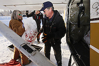 February 16, 2013  Volunteer Andi Malard helps Iditarod Air Force pilot Glen Hanson load his plane at the Willow airport as musher food, straw, HEET and people food is flown to the 4 checkpoints on the east side the Alaska Range. ..Photo Copyright Jeff Schultz  -- Do not reproduce without written permission