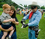 "Photo by Phil Grout..Three-year-old Wyatt Snyder of Hampstead and his Aunt Doris Snyder check out the spent shell casing ""The Lone Ranger has just fired while.shooting a hole in a fifty-cent piece to the amazement of the crowd at the.American Legion."