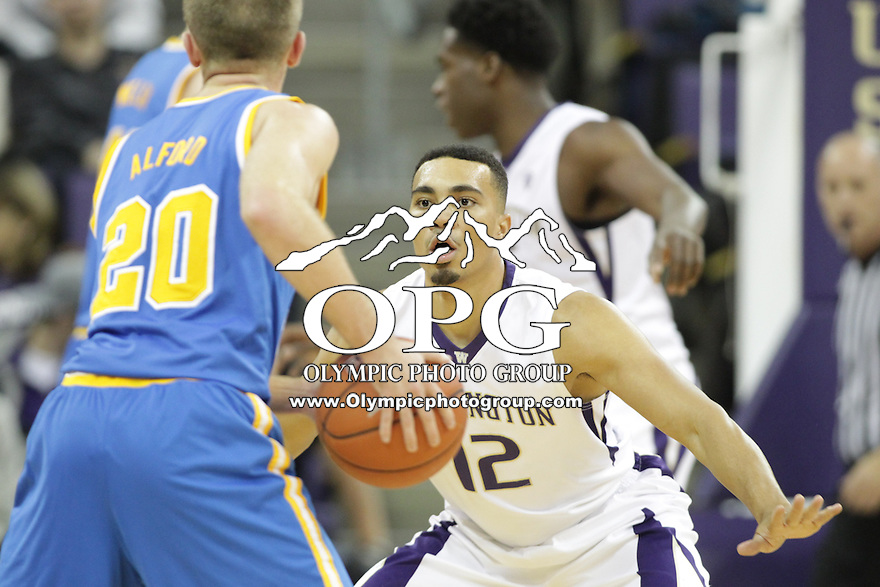 JAN 1, 2016:  Washington's #12 Andrew Andrews sets up on defense against UCLA's #20 Bryce Alford.  Washington defeated #25 ranked UCLA 96-93 in double overtime at Alaska Airlines Arena in Seattle, WA.