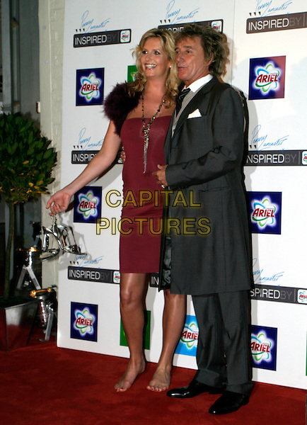 PENNY LANCASTER & ROD STEWART.Ariel - private view & VIP launch party at The Vinyl Factory, W1, London, UK..October 26th, 2005.Ref: AH.full length couple pregnant grey gray suit red dress fur stole arm over shoulder taking shoes off gesture barefoot.www.capitalpictures.com.sales@capitalpictures.com.© Capital Pictures.