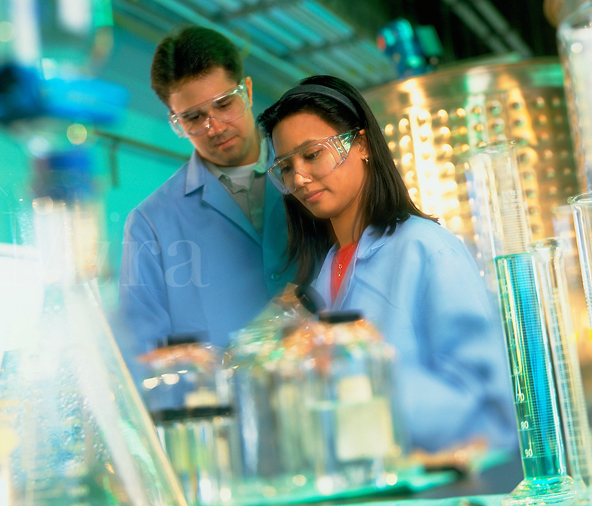 Male and female technicians in a lab setting.