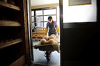 "A worker removes fireworks from the drying room at Katakai Fireworks Co., Ltd, Katakai, Japan, April 6, 2009. The company makes the world's largest firework, a 120cm round shell called a ""yonshakudama""."