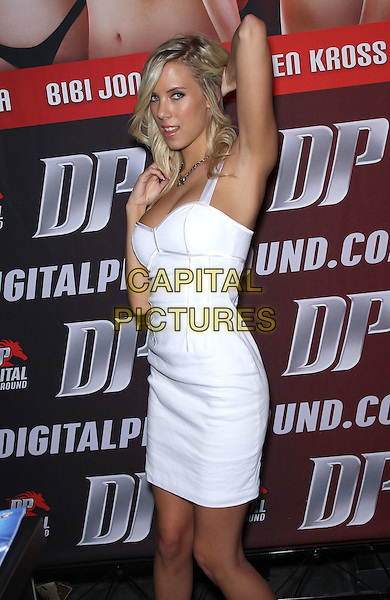 Bibi Jones.Day One of AVN Adult Entertainment Expo at the Hard Rock Hotel and Casino, Las Vegas, Nevada, USA.  .January 18th, 2012.half length white dress side 3/4 arm in air.CAP/ADM/MJT.© MJT/AdMedia/Capital Pictures.