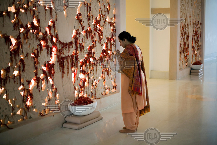 A woman offers prayers after she has tied a sacred thread to a prayer wall at Medanta - The Medicity, near New Delhi. The hospital is India's most technologically advanced multi-disciplinary hospital, founded by leading cardiac surgeon Dr Naresh Trehan.