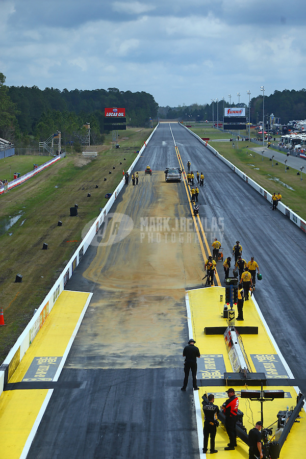 Mar 18, 2016; Gainesville, FL, USA; NHRA safety safari crews work to clean up oil on the track during qualifying for the Gatornationals at Auto Plus Raceway at Gainesville. Mandatory Credit: Mark J. Rebilas-USA TODAY Sports