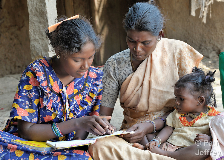Angali (left) helps Jayalakstimi, who holds her daughter Kirthana, during a women's literacy class in Nandambakkam, a tribal village in the southern India state of Tamil Nadu.