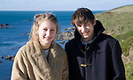Model released brother and sister twins standing together on sunny winter day, Cornwall, England, UK