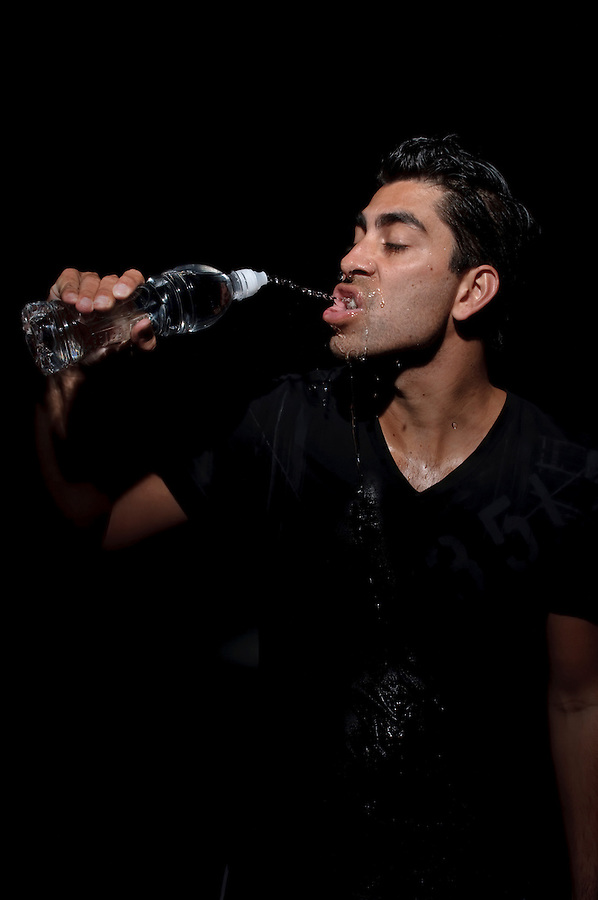 Young man desperately thirsty drinking water in black background.